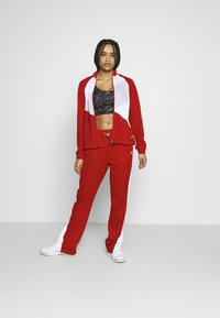 ASICS - TOKYO WARM UP  - Tracksuit bottoms - classic red/brilliant white - 1