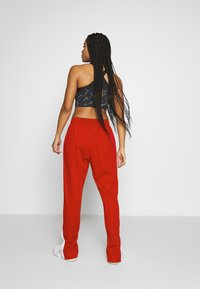 ASICS - TOKYO WARM UP  - Tracksuit bottoms - classic red/brilliant white - 2