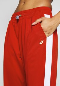 ASICS - TOKYO WARM UP  - Tracksuit bottoms - classic red/brilliant white - 5