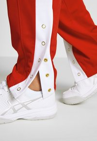 ASICS - TOKYO WARM UP  - Tracksuit bottoms - classic red/brilliant white - 3