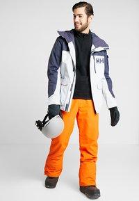 Brunotti - FOOTSTRAP MEN SNOWPANTS - Talvihousut - fluo orange - 1