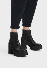 Bershka - STIEFELETTE MIT PLATEAU-ABSATZ 11116560 - Kotníková obuv na vysokém podpatku - black - 0