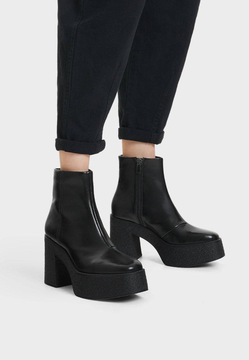 Bershka - STIEFELETTE MIT PLATEAU-ABSATZ 11116560 - Kotníková obuv na vysokém podpatku - black