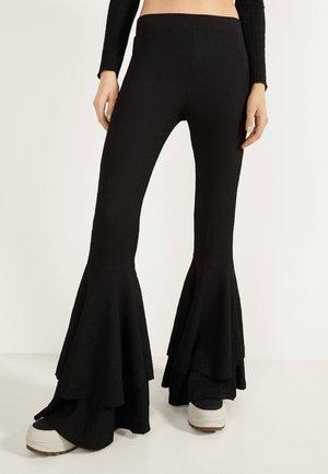 MIT VOLANTS - Trousers - black