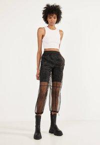 Bershka - Trousers - black - 1