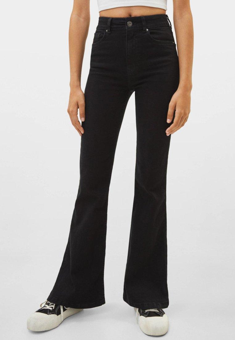 Bershka - MIT SCHLAG UND HOHEM BUND  - Flared Jeans - black