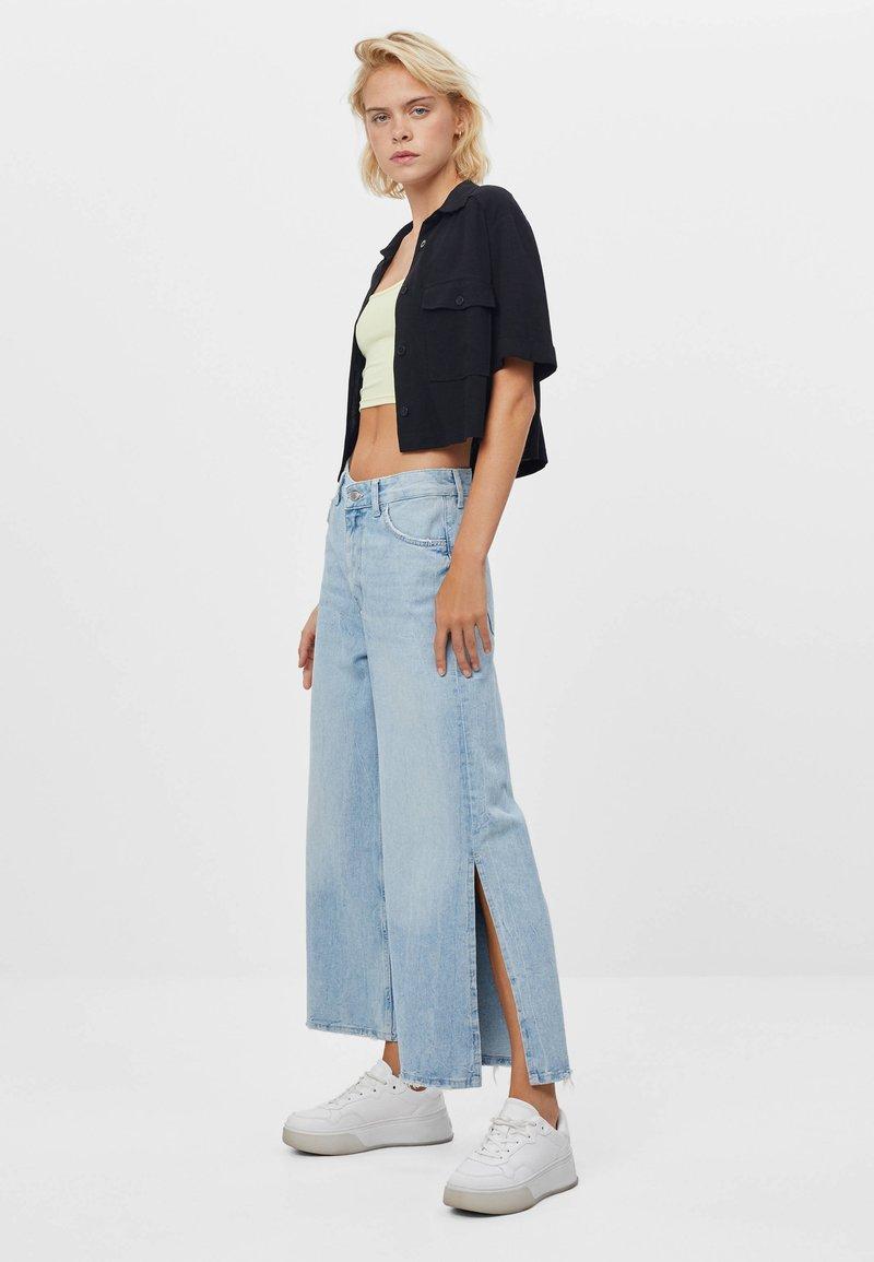 Bershka - CULOTTE MIT SCHLITZEN - Flared Jeans - blue denim