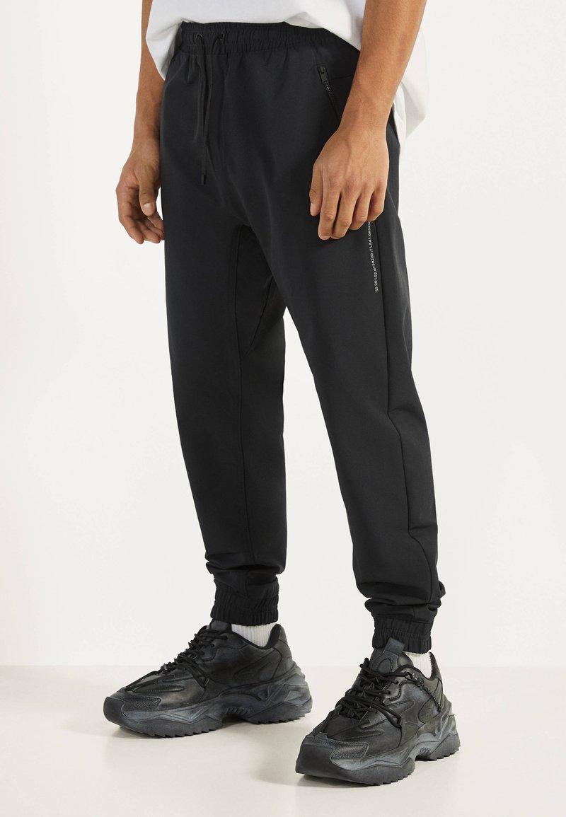 Bershka - JOGGERHOSE AUS FUNKTIONSSTOFF 00294665 - Pantalon de survêtement - black