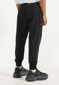 Bershka - JOGGERHOSE AUS FUNKTIONSSTOFF 00294665 - Pantalon de survêtement - black - 2