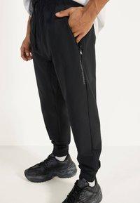 Bershka - JOGGERHOSE AUS FUNKTIONSSTOFF 00294665 - Pantalon de survêtement - black - 3
