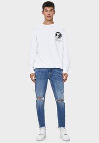 Bershka - MIT RISSEN - Jeans Skinny Fit - light blue - 1