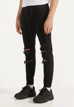 MIT RISSEN - Jeans Tapered Fit - black