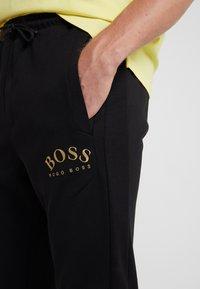 BOSS - HADIKO WIN - Pantaloni sportivi - black/gold - 5