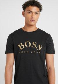 BOSS - T-shirts med print - black/gold - 4