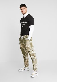 boohoo MAN - BLURRED CAMO TROUSERS WITH ELASTICATED WAIST - Teplákové kalhoty - green - 1