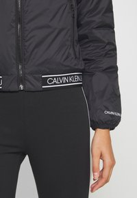 Calvin Klein Jeans - LOGO HOODED PADDED JACKET - Light jacket - black - 4