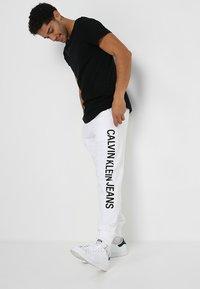 Calvin Klein Jeans - INSTITUTIONAL SIDE LOGO - Pantalon de survêtement - white - 1