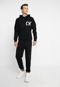 Calvin Klein Jeans - HWK INSTIT LOGO CUFF - Spodnie treningowe - black - 1