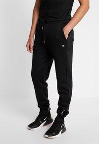 Calvin Klein Jeans - BADGE PANT - Tracksuit bottoms - black - 0