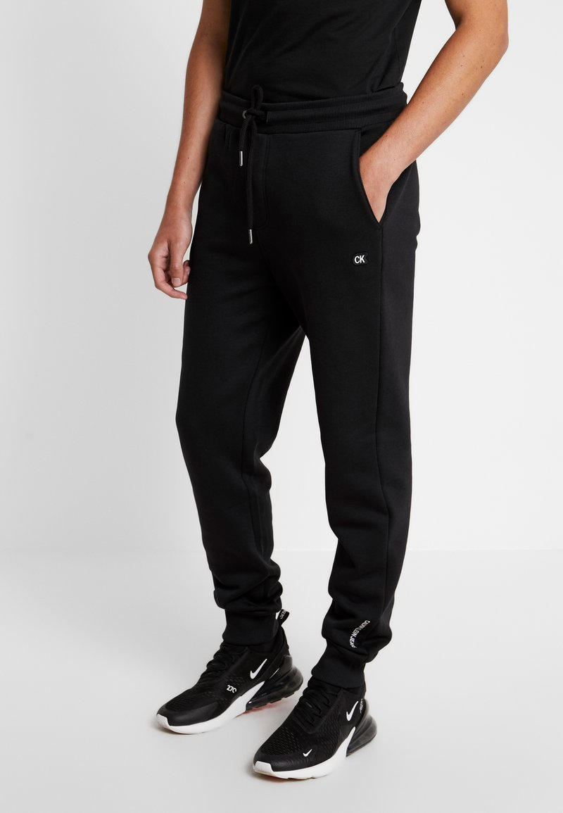 Calvin Klein Jeans - BADGE PANT - Tracksuit bottoms - black