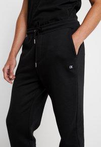 Calvin Klein Jeans - BADGE PANT - Tracksuit bottoms - black - 6