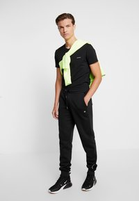 Calvin Klein Jeans - BADGE PANT - Tracksuit bottoms - black - 1