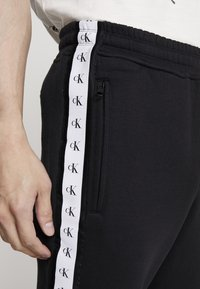 Calvin Klein Jeans - MONOGRAM TAPE PANT - Spodnie treningowe - black/white - 4