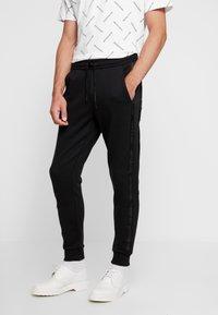 Calvin Klein Jeans - INSTIT TAPE MIX MEDIA PANT - Teplákové kalhoty - black - 0