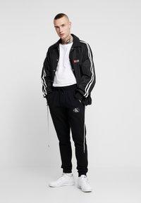 Calvin Klein Jeans - MONOGRAM PATCH PANT - Teplákové kalhoty - black - 1