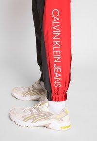 Calvin Klein Jeans - COLOR BLOCK TRACK PANT - Trainingsbroek - black/white/red - 3