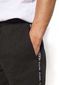Calvin Klein Jeans - SIDE LOGO - Pantalon de survêtement - black - 4