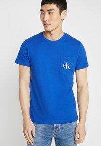 Calvin Klein Jeans - MONOGRAM POCKET SLIM TEE - T-shirt med print - blue - 0