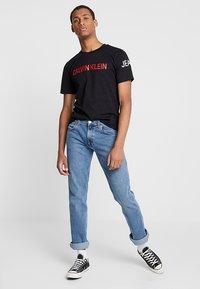 Calvin Klein Jeans - INSTIT LOGO SLEEVE TEE - Triko spotiskem - black - 1
