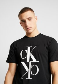 Calvin Klein Jeans - MIRRORED MONOGRAM TEE - T-shirt med print - black/white