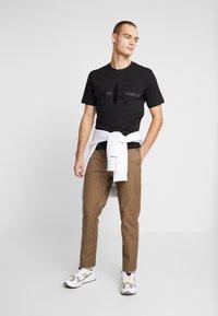 Calvin Klein Jeans - TAPING THROUGH MONOGRAM TEE - Triko spotiskem - black - 1