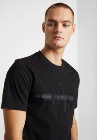Calvin Klein Jeans - TAPING THROUGH MONOGRAM TEE - Triko spotiskem - black - 4