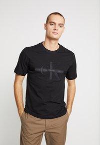 Calvin Klein Jeans - TAPING THROUGH MONOGRAM TEE - Triko spotiskem - black - 0