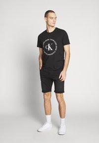 Calvin Klein Jeans - ROUND LOGO TEE - Print T-shirt - black - 1
