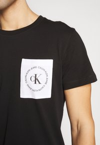 Calvin Klein Jeans - CK ROUND LOGO REG PCKT TEE - Print T-shirt - black/white - 4