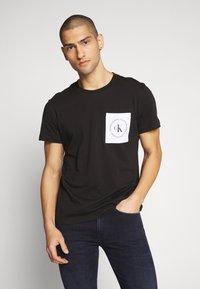 Calvin Klein Jeans - CK ROUND LOGO REG PCKT TEE - Print T-shirt - black/white - 0