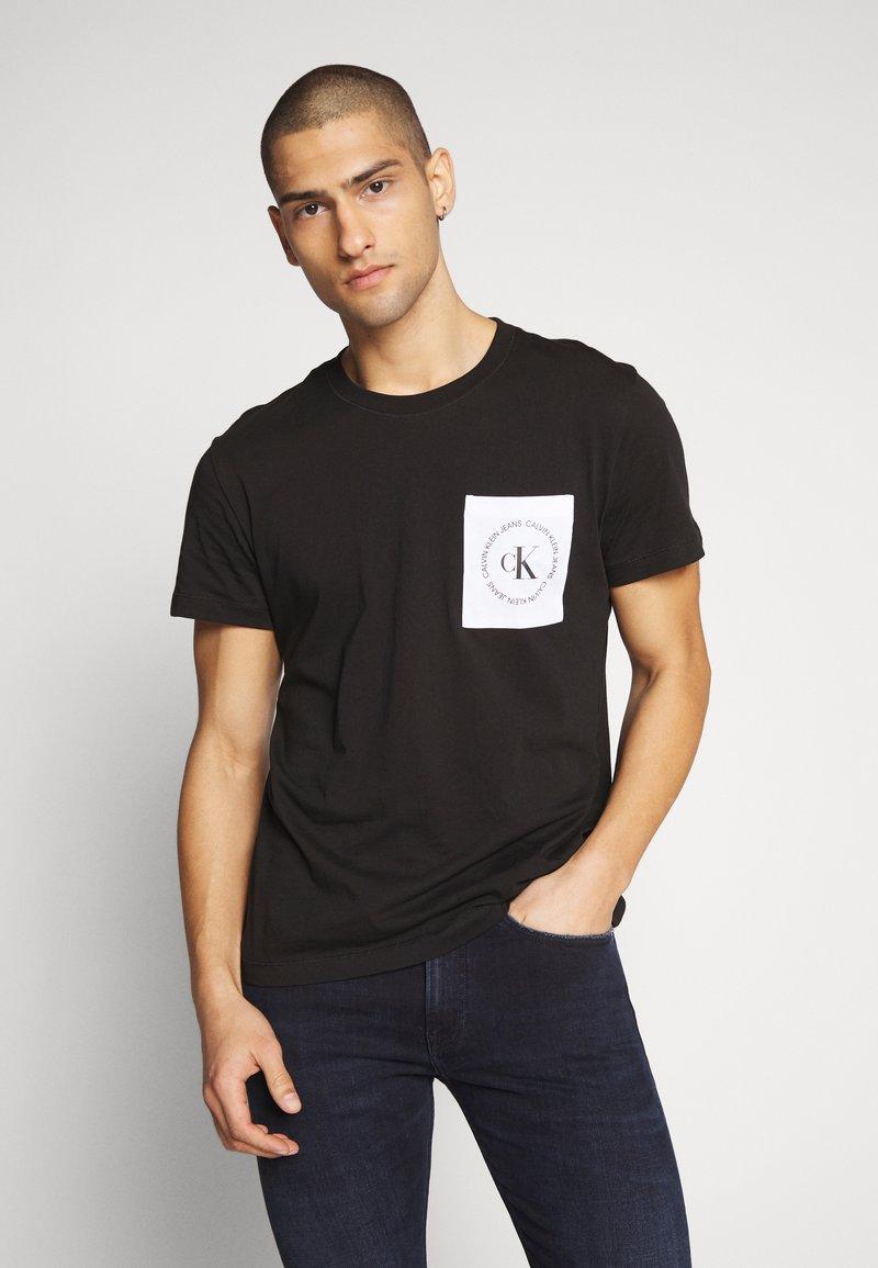 Calvin Klein Jeans - CK ROUND LOGO REG PCKT TEE - Print T-shirt - black/white