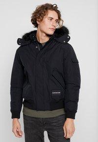 Calvin Klein Jeans - FUR TRIMMED HOODED DOWN BOMBER - Down jacket - black - 0