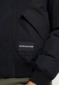 Calvin Klein Jeans - FUR TRIMMED HOODED DOWN BOMBER - Down jacket - black - 7