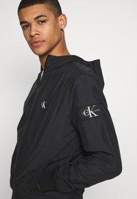 Calvin Klein Jeans - HOODED BLOCKING NYLON JACKET - Kevyt takki - black/white - 3