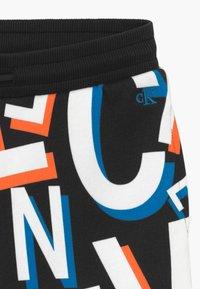 Calvin Klein Jeans - LETTER - Tracksuit bottoms - black - 3