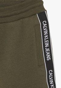 Calvin Klein Jeans - SIDE LOGO TAPE - Teplákové kalhoty - green - 3