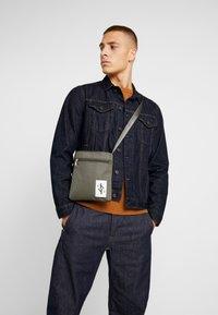 Calvin Klein Jeans - SPORT ESSENTIALS MICRO FLAT PACK - Torba na ramię - green - 1