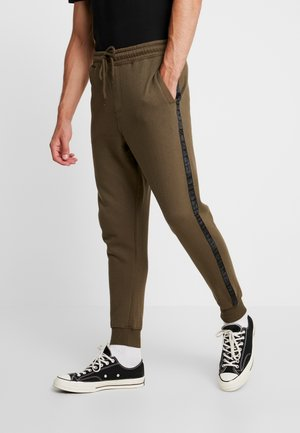 TRIPPY TRACKIE - Tracksuit bottoms - army green