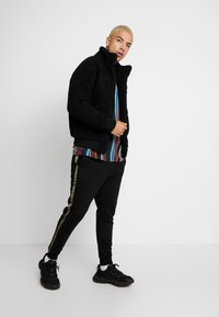 Cotton On - TRIPPY TRACKIE - Tracksuit bottoms - black - 1