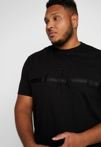 Calvin Klein Jeans Plus - PLUS TAPING THROUGH MONOGRAM TEE - T-shirt imprimé - black - 3